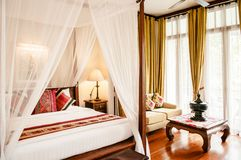 Colonial style bedroom wooden four poster bed with curtain, colo. Mar 11, 2014 BANGKOK, Thailand  : Vintage Colonial style bedroom wooden four poster bed with Royalty Free Stock Images