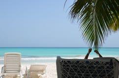Mar bonito e areia branca Um homem encontra-se na cadeira de plataforma, sustentando suas mãos, na máscara das palmeiras na praia Fotos de Stock