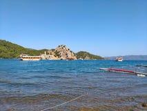 Mar, céu, barco perto do azul montanhoso pitoresco da costa e cores naturais puras do gree Fotografia de Stock
