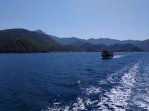 Mar, céu, barco perto do azul montanhoso pitoresco da costa e cores naturais puras do gree Imagens de Stock Royalty Free