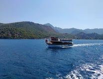 Mar, céu, barco perto do azul montanhoso pitoresco da costa e cores naturais puras do gree Imagens de Stock