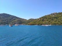 Mar, céu, barcos, perto das cores naturais puras montanhosas pitorescas do azul e do gree da costa Foto de Stock