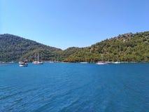 Mar, céu, barcos, perto das cores naturais puras montanhosas pitorescas do azul e do gree da costa Foto de Stock Royalty Free
