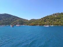 Mar, céu, barcos, perto das cores naturais puras montanhosas pitorescas do azul e do gree da costa Fotos de Stock