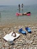 Mar, café, libro y familia el vacaciones Imagen de archivo libre de regalías