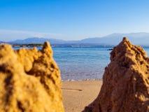 Mar calmo e uma praia vazia - castelos de areia pequenos na parte dianteira fotos de stock royalty free