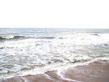Mar cinzento da cor com as ondas espumosas do branco e a areia marrom da cor Fotos de Stock