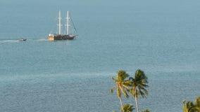Mar con el barco de navegación y las plantas exóticas tropicales Desde arriba de vista del océano azul tranquilo con la nave de m metrajes