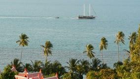 Mar con el barco de navegación y las plantas exóticas tropicales Desde arriba de vista del océano azul tranquilo con la nave de m almacen de video