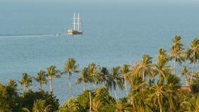 Mar con el barco de navegación y las plantas exóticas tropicales Desde arriba de vista del océano azul tranquilo con la nave de m almacen de metraje de vídeo