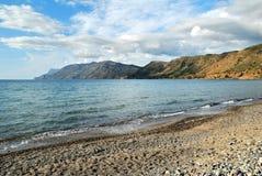 Mar con una playa y las colinas Imagenes de archivo