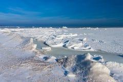 Mar congelado do inverno sob a neve durante o dia ensolarado fotografia de stock royalty free