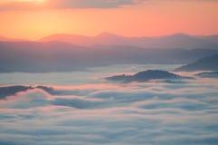 Mar das nuvens na montanha no nascer do sol Carpathians, o cume Bor