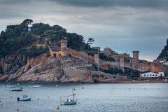 Mar de Buch com barcos a vila famosa de Tossa de Mar em Costa Brava na noite, Catalonia, Espanha foto de stock royalty free