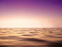 Mar de la paz y cielo púrpura en cierre determinado del tiempo del sol para arriba como fondo Imagen de archivo libre de regalías