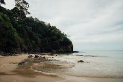 Mar de la playa de Sandy en la colina verde del fondo Océano de la orilla de Sandy y colina verde Foto de archivo libre de regalías