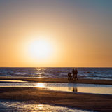 Mar de la puesta del sol y siluetas de pares con el carro de bebé Foto de archivo libre de regalías