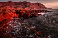 Mar de tormenta en la puesta del sol en la costa de la montaña Fotos de archivo libres de regalías