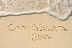 Mar del Caribe escrito en arena en la playa Imágenes de archivo libres de regalías