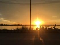 Mar do por do sol e silhueta do amigo fotografia de stock