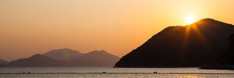 Mar e montes no por do sol Imagens de Stock Royalty Free