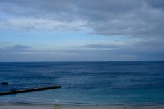 Mar e nuvens azuis no céu Imagens de Stock
