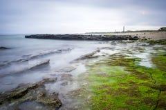 Mar e rocha longos do exporsure na praia Fotos de Stock Royalty Free