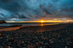 Mar e rochas do por do sol Foto de Stock