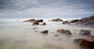Mar e rochas enevoados fotografia de stock