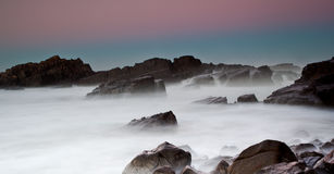 Mar e rochas enevoados imagens de stock