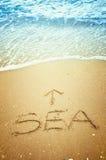Mar e seta escritos na areia foto de stock