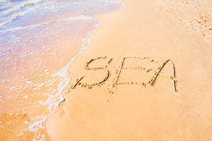 Mar escrito en la arena en la costa, fondo Fotos de archivo libres de regalías