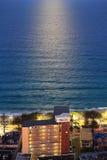 mar Escuro-azul que cintila na Lua cheia nos surfistas P Fotografia de Stock Royalty Free