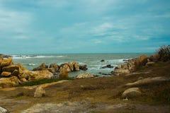 Mar hermoso con las ondas y las montañas, piedra enorme Silueta del hombre de negocios Cowering Mui Ne, Phan Thiet, Vietnam Fotos de archivo libres de regalías