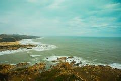 Mar hermoso con las ondas y las montañas Silueta del hombre de negocios Cowering Mui Ne, Phan Thiet, Vietnam Imagen de archivo