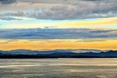 Mar, montaña y cielo en oscuridad de la tarde Imagenes de archivo