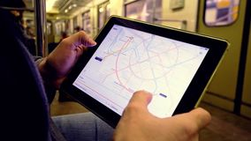 Man in underground examines the metro map. MAR 28, 2018, MOSCOW, RUSSIA: Man in underground examines the metro map using the tablet computer, people passing by stock video footage