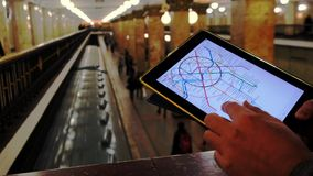 Man in underground examines the metro map. Mar 28, 2018, Moscow, Russia: Man in underground examines the metro map using the tablet, people passing by stock video