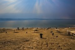 Mar muerto Jordania 20-09-2017 Una playa ancha con los guijarros y la arena lleva al mar muerto en un cielo extraño que haga que  Imagenes de archivo