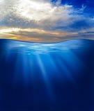 Mar ou oceano subaquático com céu do por do sol foto de stock royalty free