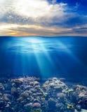 Mar ou oceano subaquático com céu do por do sol fotografia de stock