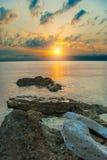 Mar, pedras e o sol de ajuste Fotos de Stock Royalty Free