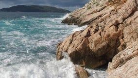 Mar puro das águas azuis, ondas litorais que quebram e que espirram a aventura em rochas da ressaca da costa de mar footage verão Imagem de Stock Royalty Free