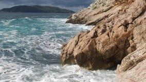 Mar puro das águas azuis, ondas litorais que quebram e que espirram a aventura em rochas da ressaca da costa de mar footage verão Foto de Stock Royalty Free