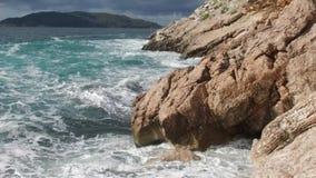 Mar puro de las aguas azules, ondas de Coastal que rompen y que salpican aventura en rocas de la resaca de la costa de mar cantid almacen de video
