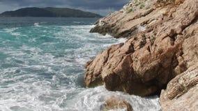 Mar puro de las aguas azules, ondas de Coastal que rompen y que salpican aventura en rocas de la resaca de la costa de mar cantid almacen de metraje de vídeo