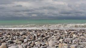 Mar que rabia, ondas que baten contra la orilla, nubes en el cielo almacen de video
