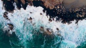 Mar que salpica contra altas rocas en una costa metrajes