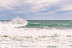 Mar tempestuoso con agua hermosa de la turquesa y wa de rociadura escénico Fotos de archivo