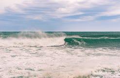 Mar tempestuoso con agua hermosa de la turquesa y wa de rociadura escénico Imagenes de archivo